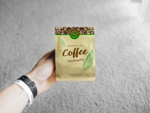 Hand Holding Coffee Bag Packaging Free Mockup