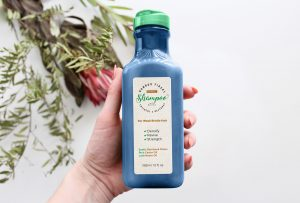 Hand Holding Organic Shampoo Bottle Free Mockup