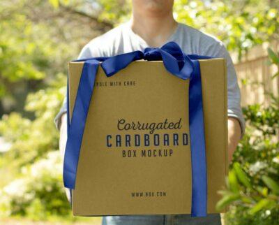 Hand Holding Corrugated Cardboard Box Free Mockup